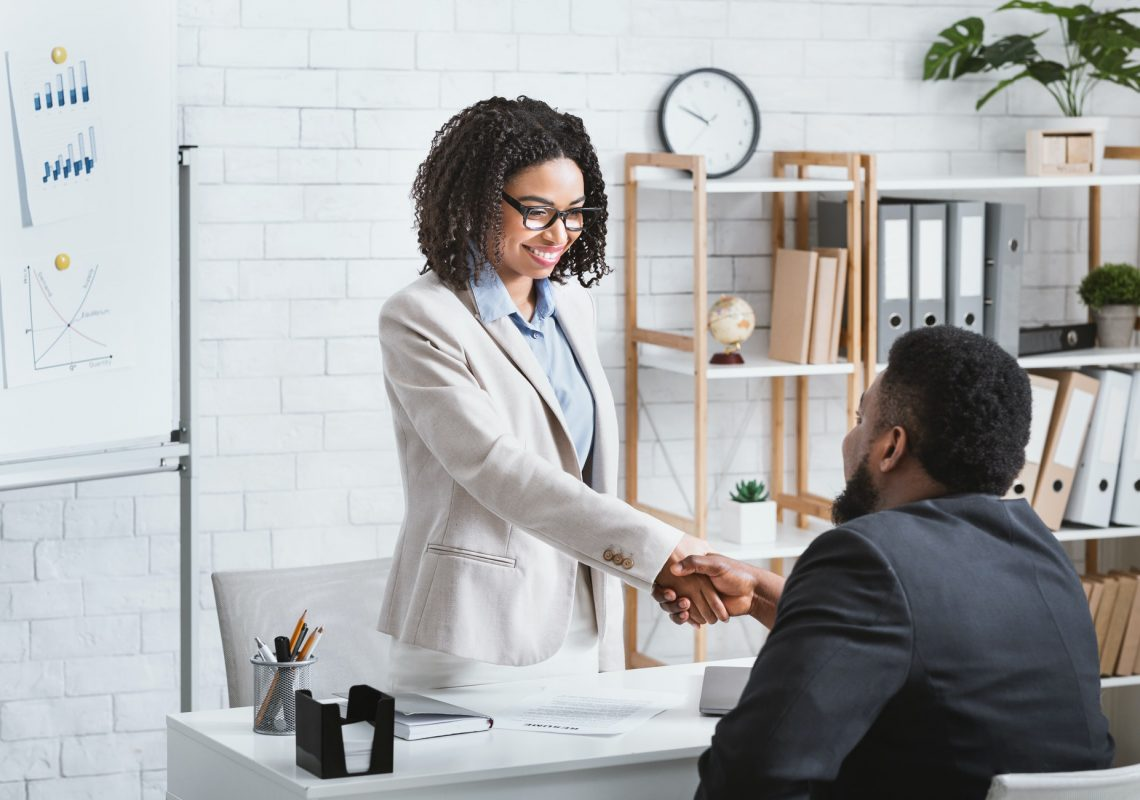 Black hiring manager shaking hands with successful vacancy candidate after work interview at office